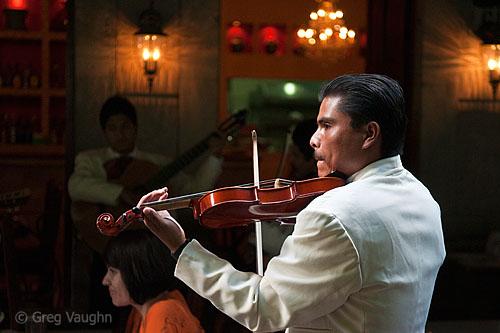 Mariachi serenading a couple in a restaurant.