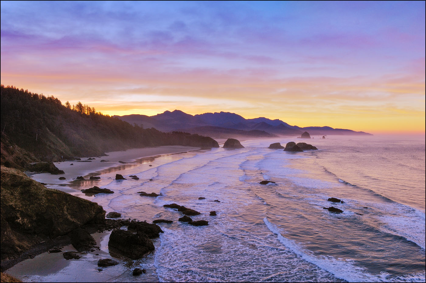 View of Crescent Beach, Cannon Beach, Haystack Rock and coast to Hug Point from Ecola State Park at sunrise; Oregon.