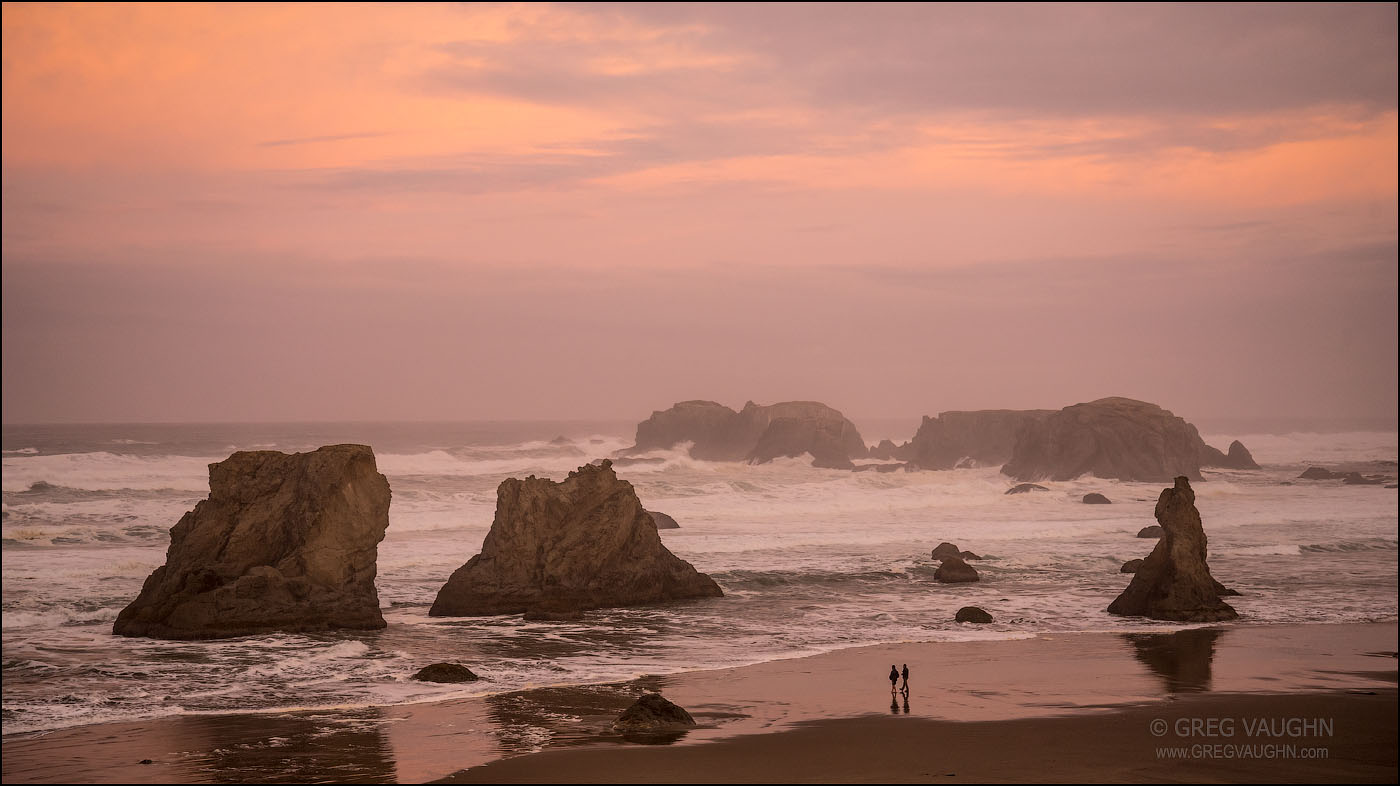 Two young men walking on Bandon Beach on a stormy dawn; Oregon Coast.
